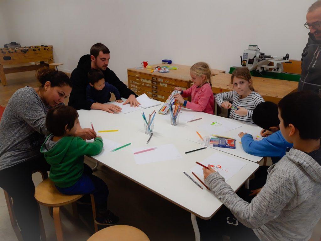 Kinder und Erwachsene malen am Tisch bei der Malaktion Abenteuer Lernen eV