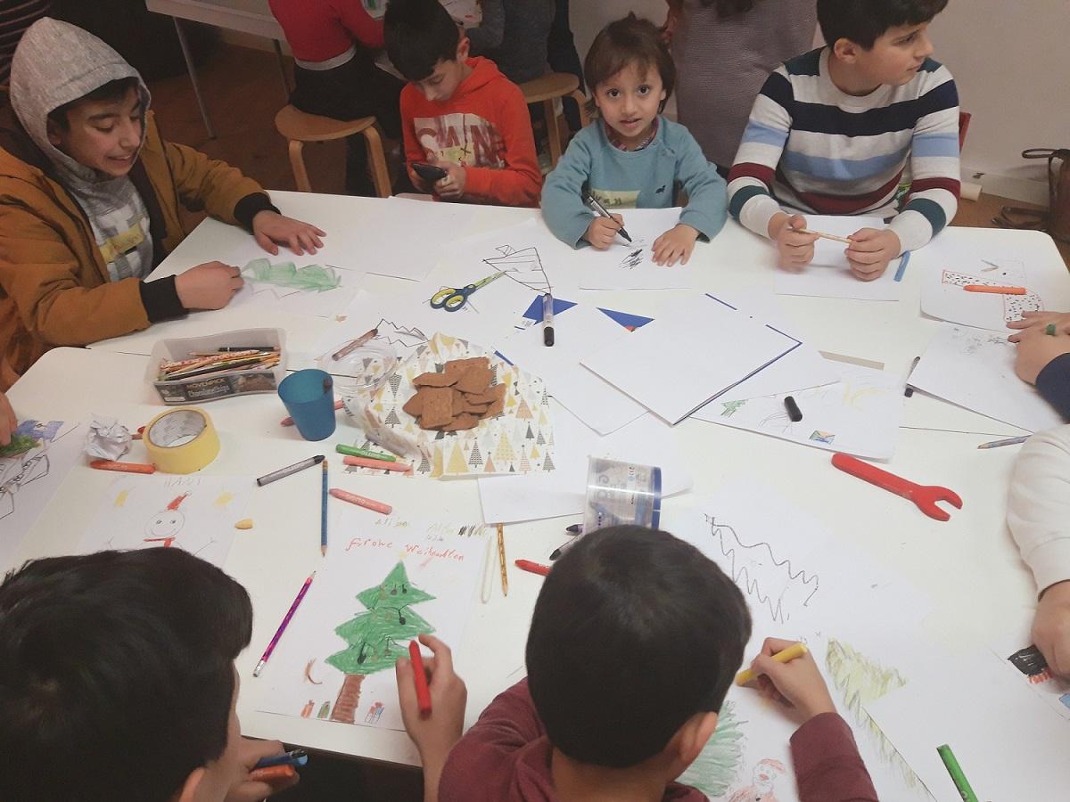 Jungen malen Weihnachtsmotive am Tisch bei der Spendenaktion von synalis_klein